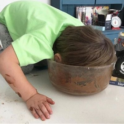 Boy sticking his head in a bowl of cake batter