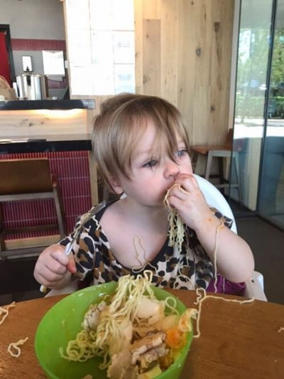 Picky toddler tasting new food at restaurant