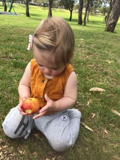 Toddler girl tasting an apple