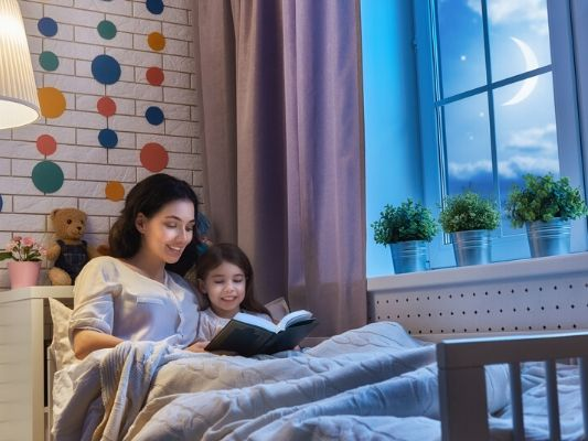 Mother and daughter reading book at bedtime