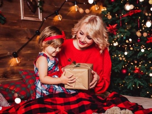 Mother and daughter opening Christmas present together
